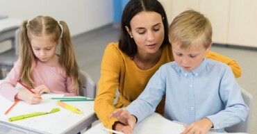 high-angle-teacher-helping-little-boy-class_23-2148668660